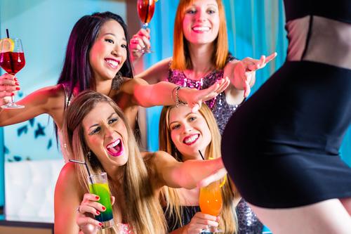Drunk women with fancy cocktails in strip club