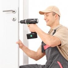 Llocksmith screwing a screw on lock of a door